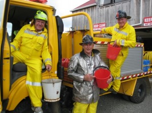 Merv Sutton wearing modern yellow fire fighting helmet, Glenn Burt and Nick Gawler wearing the black helmets issued 25 years ago.  All three carrying the sort of buckets originally scrounged 30 years ago.