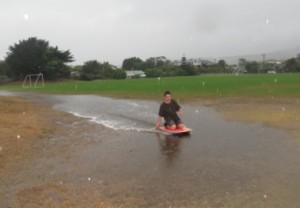 Matt, a young Raumati Beach resident ,takes advantage of the flood-waters in Weka Park to go water boarding