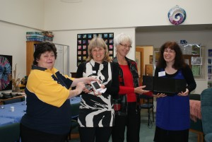 Members of the local Lions Club present audio equipment to Linda Miller, right, at the  Mary Potter Hospice Kapiti base.