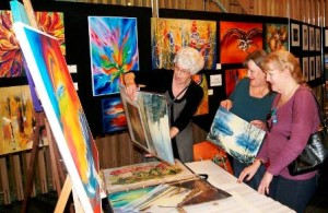 Artist Lydia bMcallister with her artworks and her sisters Margo (l) and Sue